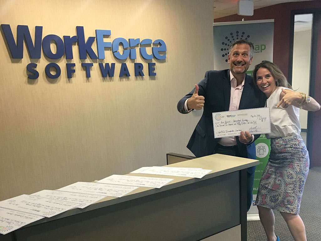 Mike Morini, CEO of WorkForce Software & Alexis Glick, CEO of GENYOUth.org finish signing the grant checks.